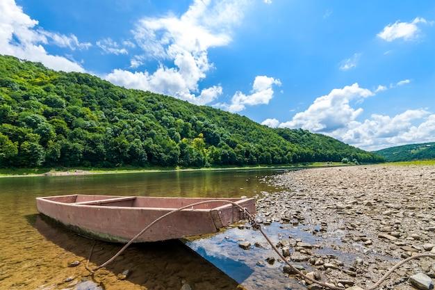 Velho barco na água limpa do rio com colinas cobertas de floresta atrás