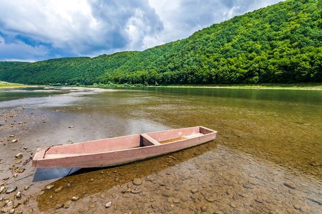 Velho barco na água limpa do rio com floresta coberta de colinas atrás.