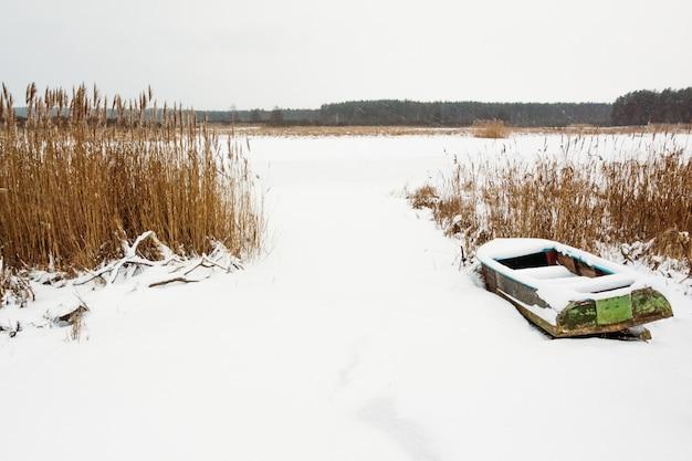 Velho barco na margem de um rio congelado com canas