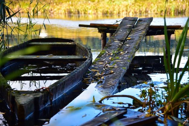 Velho barco podre no rio no outono