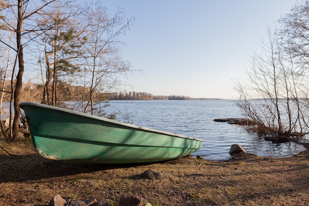 Velho barco verde na costa do lago