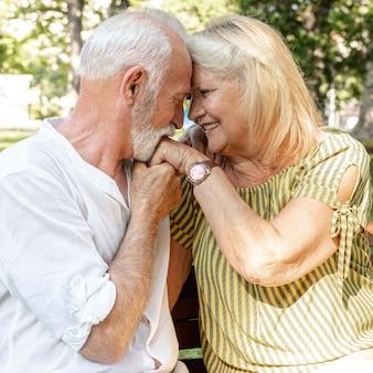 Velho beijando a mão de mulher