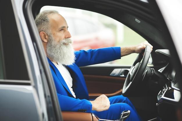 Velho bonito dentro do carro. macho maduro barbudo no automóvel. empresário confiante, comprando o carro.
