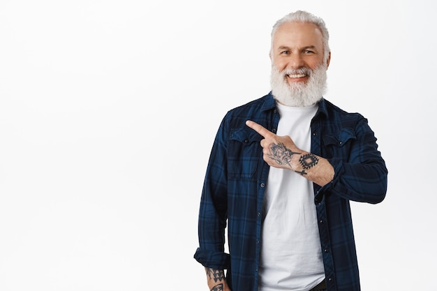 Velho bonito e barbudo, cara hipster com tatuagens apontando para a esquerda na oferta promocional, mostrando a faixa do logotipo ao lado, sorrindo satisfeito, recomendando clique no link, em pé sobre uma parede branca
