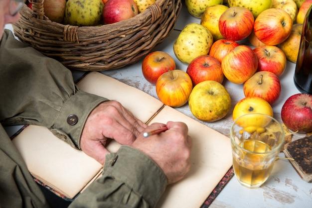 Velho caderno com cesta de maçãs e garrafas de cidra