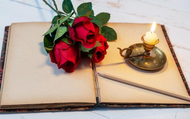 Velho caderno, rosas e vela pequena, conceito romântico