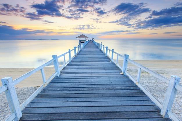 Velho cais da ponte de madeira contra o belo céu do sol