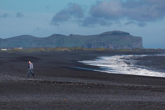 Velho caminhando na areia preta de uma praia na islândia