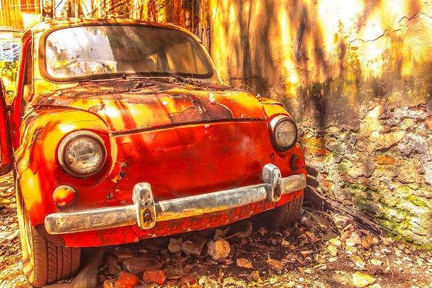 Velho carro enferrujado na frente da parede suja