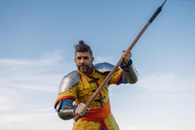 Velho cavaleiro medieval com armadura segurando machado