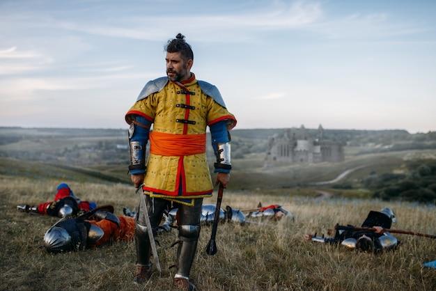 Velho cavaleiro medieval em armadura olha para os mortos após uma grande batalha. antigo guerreiro com armadura posando no campo