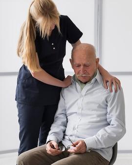 Velho chorando em uma casa de repouso com uma enfermeira consolando-o