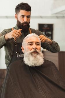 Velho cliente recebendo o corte de cabelo no salão de cabeleireiro
