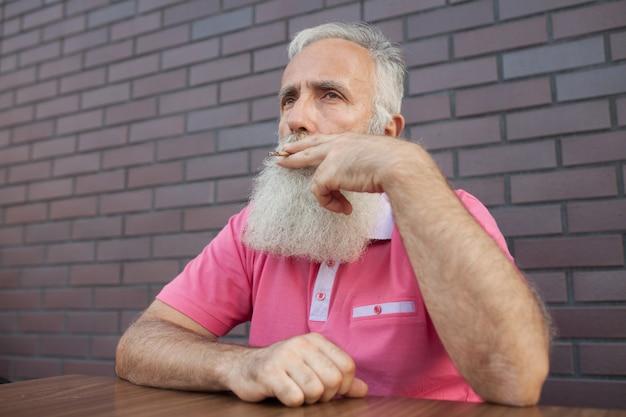 Velho com barba e bigodes em um fumo de camiseta rosa.
