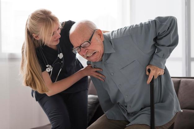 Velho com dor ajudado pela enfermeira