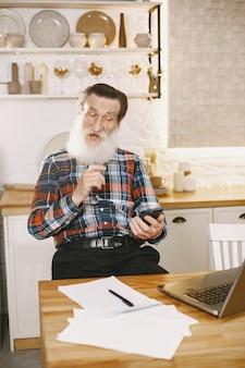 Velho com laptop. avô sentado em uma decoração de natal. homem com telefone celular.