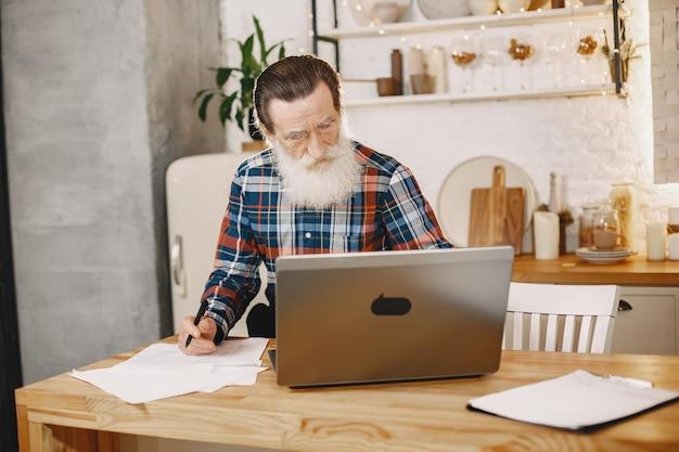 Velho com laptop. avô sentado em uma decoração de natal. homem com uma camisa de cela.