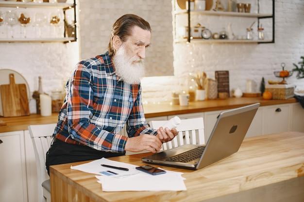 Velho com laptop.