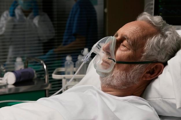 Velho com respirador em uma cama de hospital