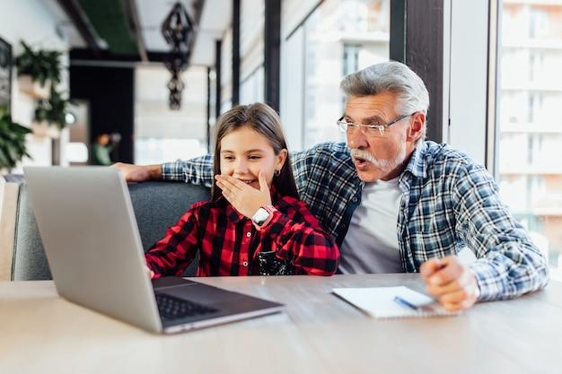 Velho com sua neta usando tablet fazendo videochamada para criança.