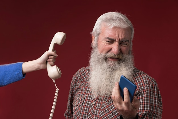 Velho com telefone novo e antigo