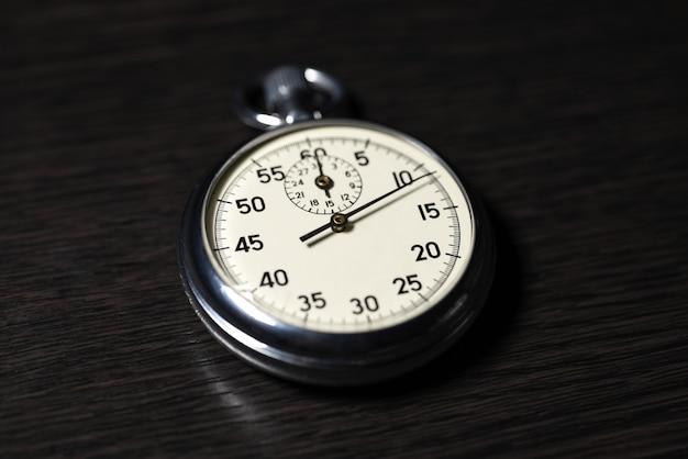 Velho cronômetro analógico encontra-se em uma superfície de madeira escura, close-up