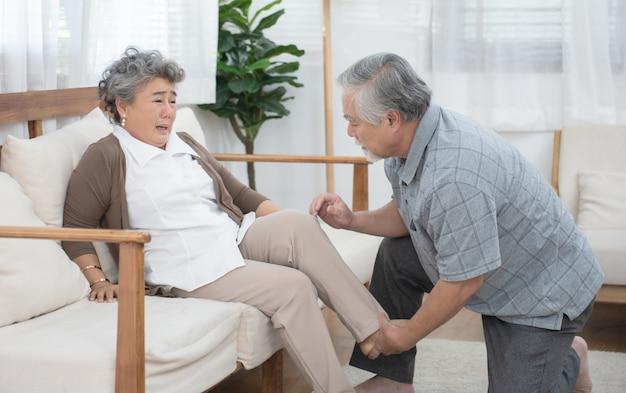 Velho cuidar de mulher mais velha depois de machucar na perna.