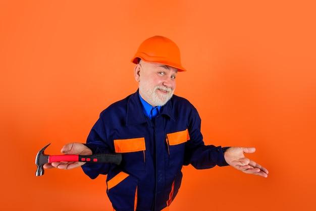 Velho da indústria de construção civil construtor de capacete com engenheiros de martelo trabalhando no conserto