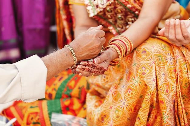 Velho derrama algo nas mãos da mulher indiana vestida