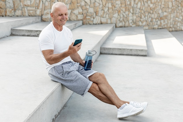 Velho descansando olhando para seu telefone tiro completo
