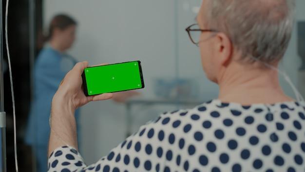Velho doente segurando um dispositivo de tela verde na instalação da enfermaria do hospital para tratamento médico mais velho pa ...