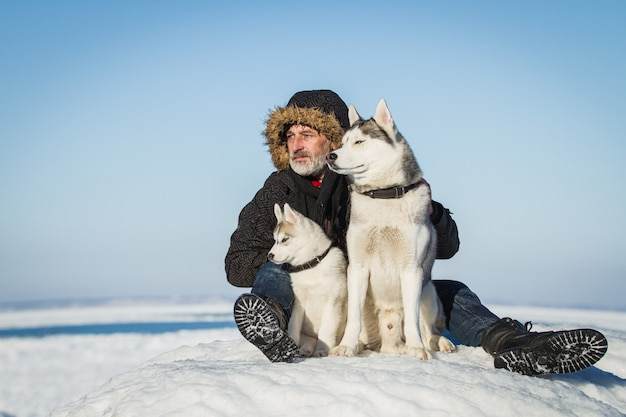 Velho e cães de trenó em um bloco de gelo.