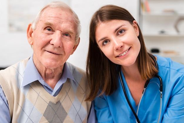 Velho e enfermeira olhando para a câmera