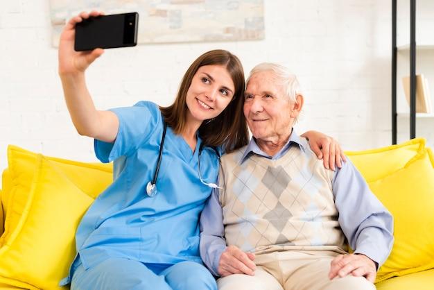 Velho e enfermeira tomando uma selfie