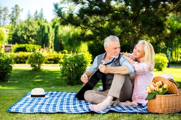 Velho e mulher em um cobertor no piquenique