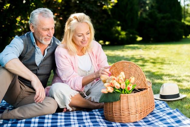 Velho e mulher olhando uma cesta de piquenique