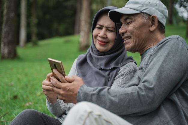 Velho e mulher usando telefone celular no parque