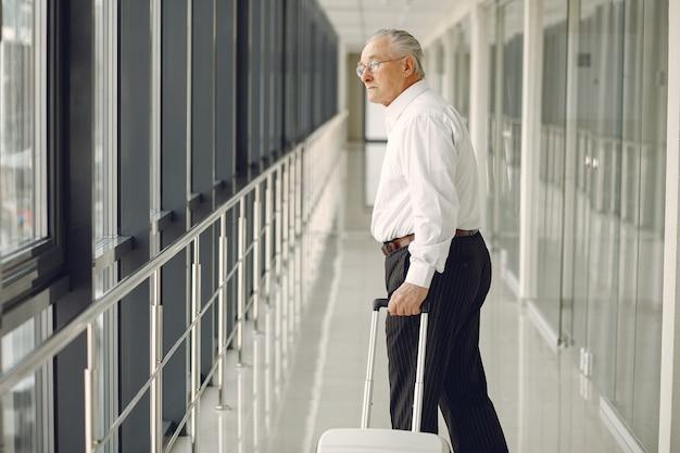 Velho elegante no aeroporto com uma mala