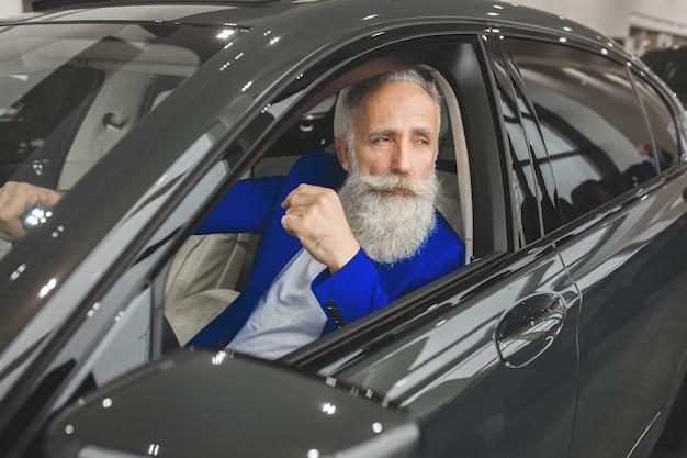 Velho elegante no carro de luxo. macho com barba e bigode dirigindo automóvel. salão de vendas de carros.