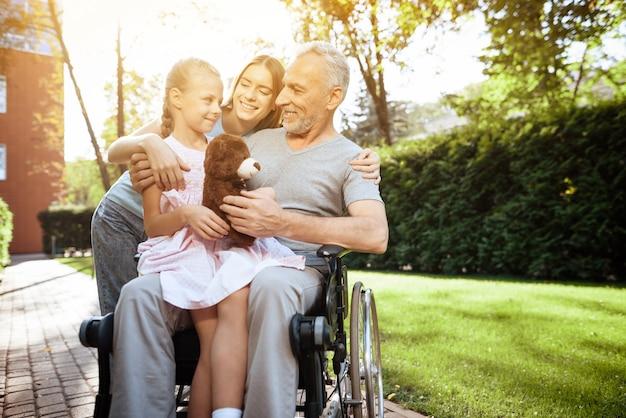 Velho em cadeira de rodas com a família ao ar livre