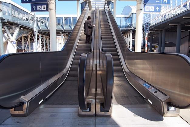Velho em traje preto usando escada rolante no aeroporto