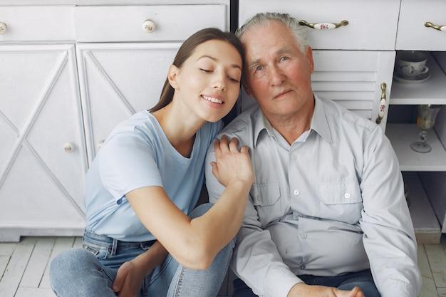 Velho em uma cozinha com jovem neta