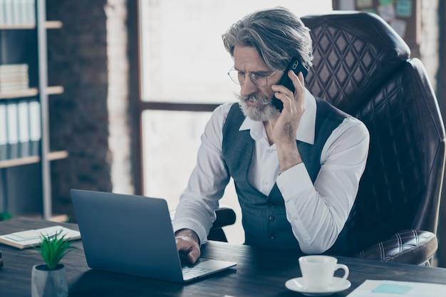 Velho empresário focado em falar de laptop no celular no escritório