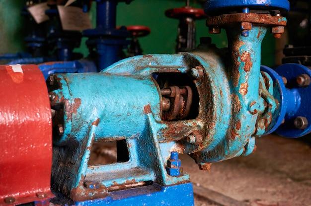 Velho, enferrujado com arranhões, a bomba d'água pintada de azul no oleoduto de água fria pintada de azul.