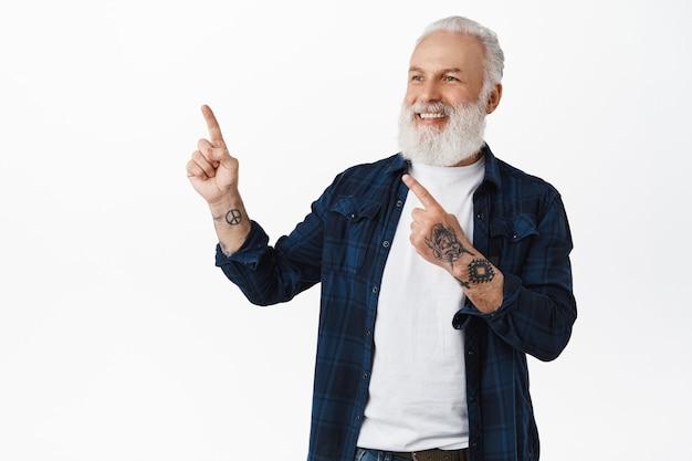 Velho estiloso com barba e tatuagens, apontando para o canto superior esquerdo e parecendo satisfeito, acena com a cabeça em aprovação para o logotipo ou texto promocional da empresa, em pé sobre uma parede branca