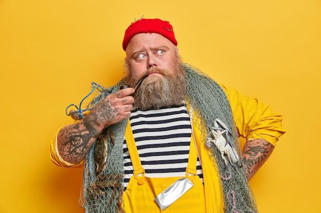 Velho experiente marinheiro barbudo pensa no dia seguinte no mar, posa com equipamento de pesca, fuma cachimbo, vestido de macacão, chapéu vermelho
