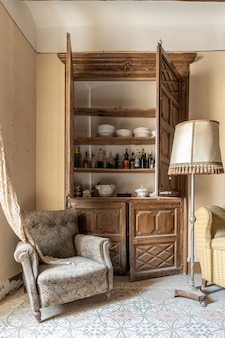 Velho guarda-roupa de uma casa clássica com bebidas e um sofá confortável e velho