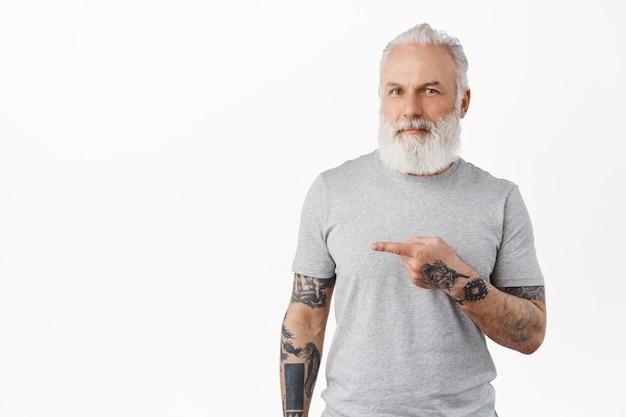 Velho hippie com barba comprida mostrando propaganda e sorrindo satisfeito, recomendando companhia, em pé sobre uma parede branca