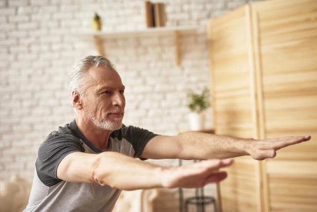 Velho homem alongamento e agachamento exercícios em casa.