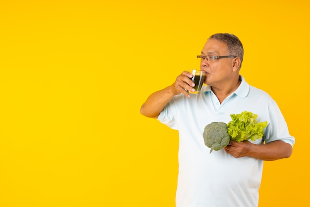 Velho homem asiático mostra suco de vegetais, tailandeses com idades entre mostrando o copo de bebidas saudáveis e segurando a salada no copyspace amarelo